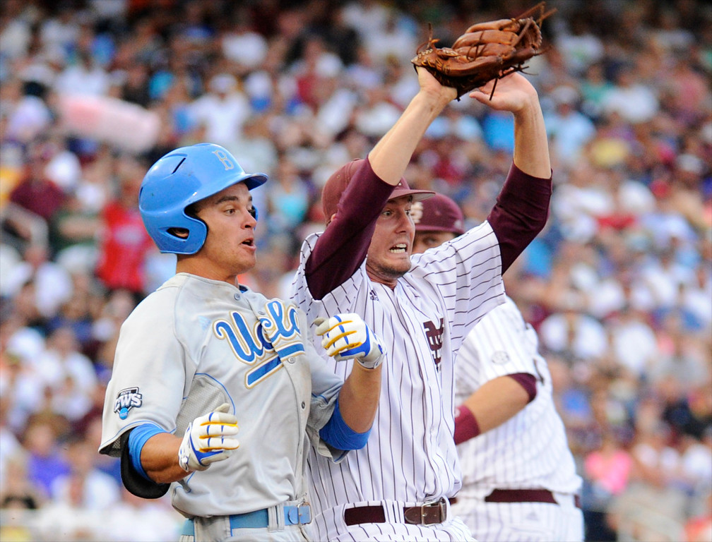 . Mississippi State pitcher Chad Girodo, right, and  UCLA base runner Kevin Kramer react after racing for first base in the second inning of Game 1 of the NCAA College World Series best-of-three finals, Monday, June 24, 2013, in Omaha, Neb. Kramer was out on the play. (AP Photo/Francis Gardler)