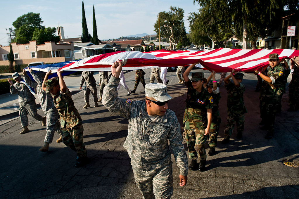 . Local cadets and servicemen and women parade with the American flag along Whittier Boulevard to the City Park Veterans Memorial to pay tribute to those killed on Sept. 11, 2001, in Montebello on Wednesday evening, Sept. 11, 2013. (Photo by Watchara Phomicinda/ San Gabriel Valley Tribune)