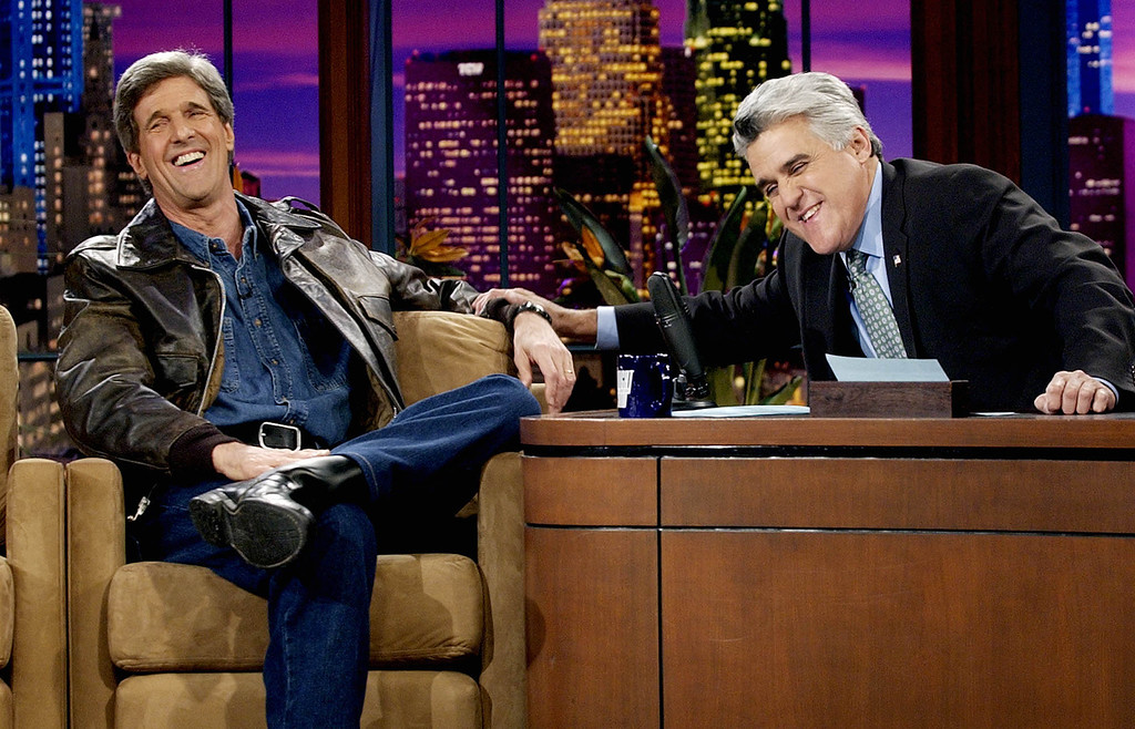 ". Wearing a leather jacket over a denim shirt and pants that he wore while making his entrance driving a motorcycle onstage, presidential candidate Sen. John Kerry, D-Mass., shares a laugh with ""Tonight Show\"" host Jay Leno at NBC studios in Burbank, Calif., Tuesday, Nov. 11, 2003.  (AP Photo/Reed Saxon)"