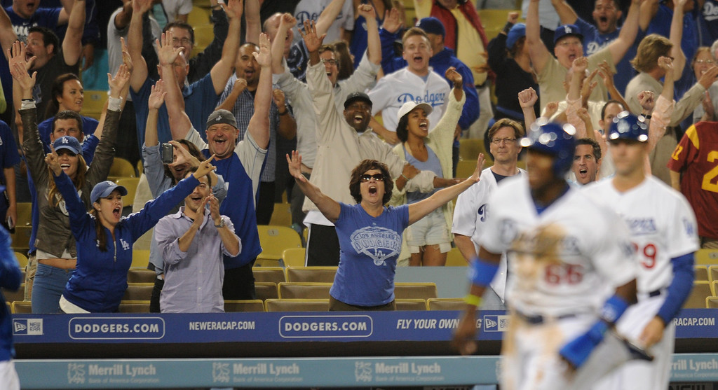 . Fans cheer as Yasiel Puig rounds 3rd base on his way home after being driven in by Adrian Gonzalez in the 12 inning for win. Fans at Dodger Stadium have been treated to a lot of excitement. The Dodgers defeated the New York Mets 5-4 in 12 innings Wednesday night at Dodger Stadium in Los Angeles, CA. 8/14/2013   (John McCoy/LA Daily News)