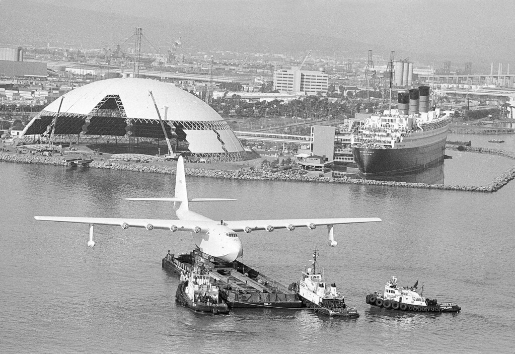 """. \""""Spruce Goose,\"""" the flying boat that belonged to the late millionaire Howard Hughes, sits perched on a barge as it was eased across the harbor in Long Beach, Calif., Feb. 11, 1982, on the way to its new display home, the large aluminum dome in left background.  At right background is the former luxury liner Queen Mary, its decks filled with sightseers watching the cross-channel move.  (AP Photo/Wally Fong)"""