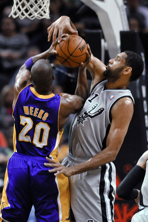 . San Antonio Spurs forward Tim Duncan blocks a shot attempt by Los Angeles Lakers guard Jodie Meeks during the first half of an NBA basketball game Friday, March 14, 2014, in San Antonio. (AP Photo/Bahram Mark Sobhani)