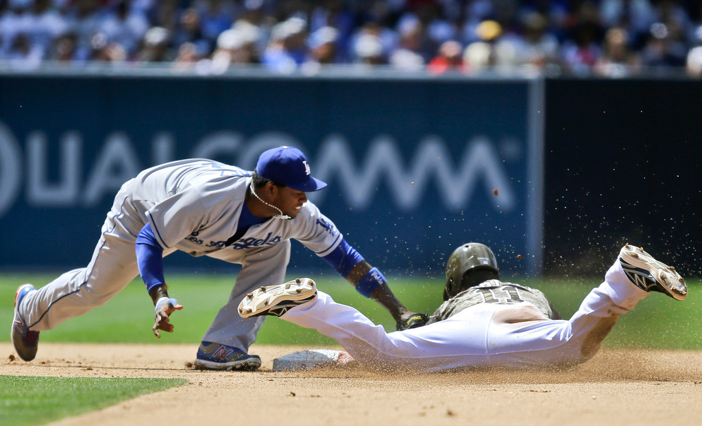 . San Diego Padres\' Logan Forsythe is tagged out by Los Angeles Dodgers shortstop Hanley Ramirez,left, while trying to steal second in the sixth inning of a baseball game in San Diego, Sunday, June 23, 2013. (AP Photo/Lenny Ignelzi)