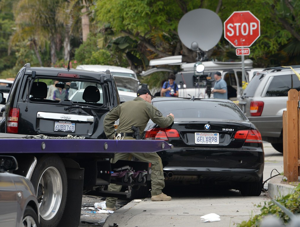 ". An investigator inspects a suspected gunman\'s car on May 24, 2014, after a drive-by shooting in Isla Vista, California, a beach community next to the University of California Santa Barbara. Seven people, including the gunman, were killed and seven others wounded in the May 23 mass shooting, Santa Barbara County Sheriff Bill Brown said Saturday. Brown said at a pre-dawn press conference that the shooting in the town of Isla Vista ""appears to be a mass murder situation.\"" Driving a black BMW, the suspect opened fire on pedestrians from his vehicle at several locations in the town.           (ROBYN BECK/AFP/Getty Images)"