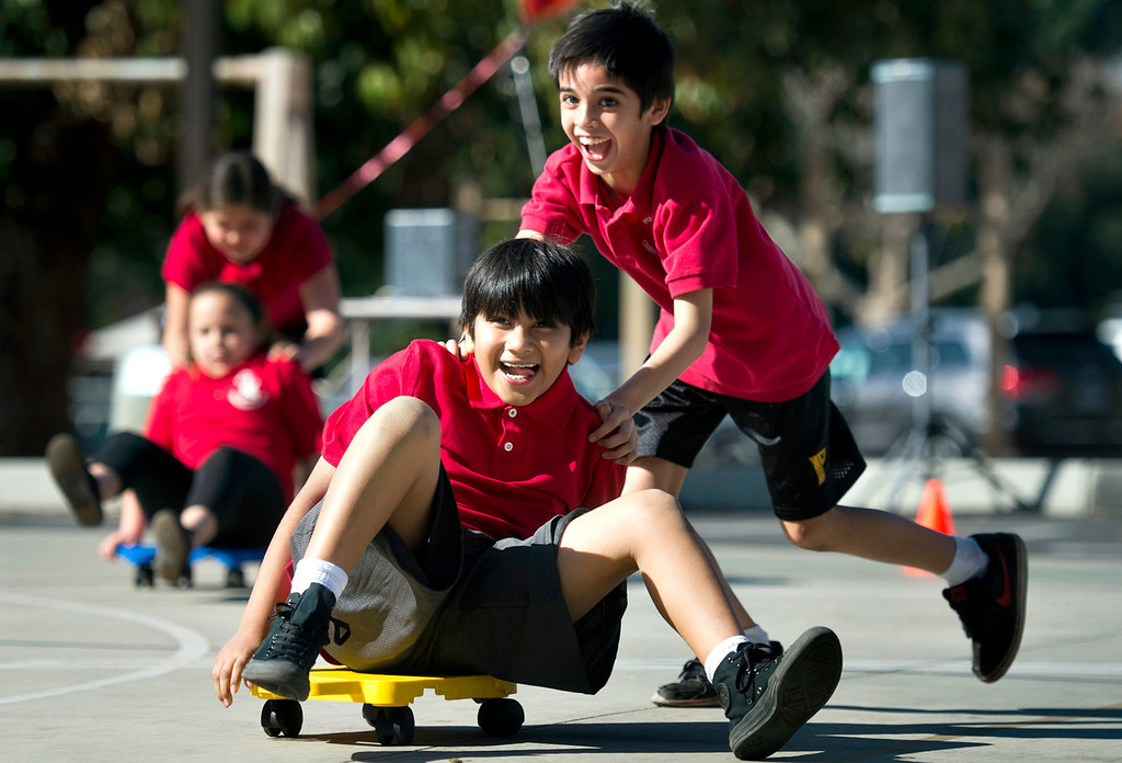 . Luke Moreno pushes classmate Isaac Huerta, both 9, as they exercise during floor scooter relay at Plymouth Christian School in Whittier on Friday, Feb. 14, 2014. The school held the exercise event to promote good health. (Photo by Watchara Phomicinda/ Whittier Daily News)