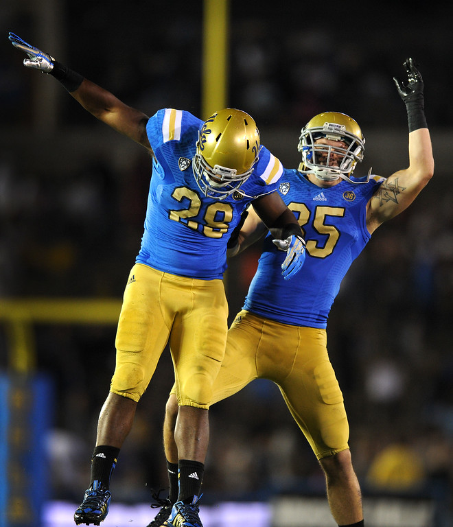 . UCLA RB Malcolm Jones, left, celebrates one of his fourth quarter touchdowns against New Mexico State, Saturday, September 21, 2013, at the Rose Bowl. (Photo by Michael Owen Baker/L.A. Daily News)