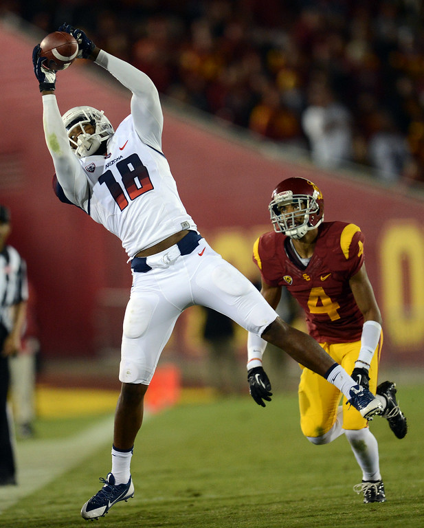 . Arizona\'s Terrence Miller #18 hauls in a pass as USC\'s  Torin Harris #4 defends during their game at the Los Angeles Memorial Coliseum Thursday, October 10, 2013. USC defeated Arizona 38-31. (Photo by Hans Gutknecht/Los Angeles Daily News)