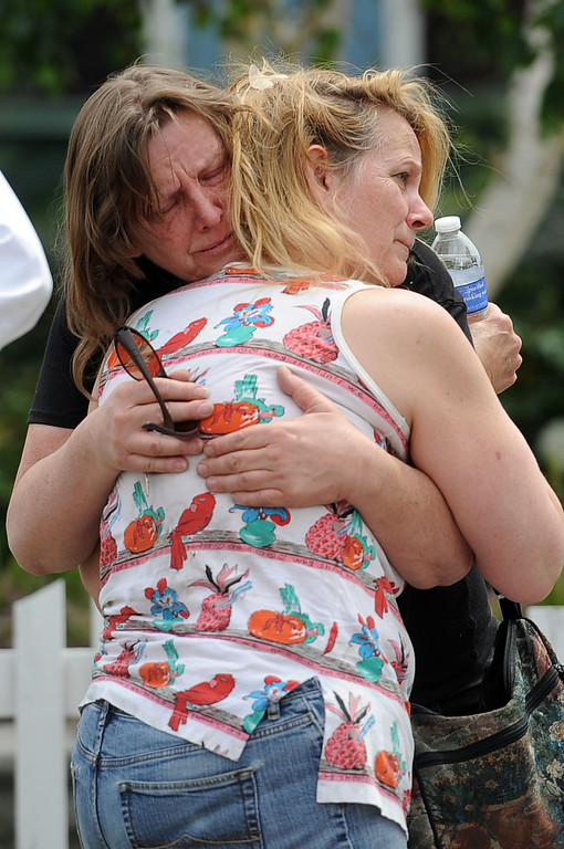 . A homeowner is consoled after a fire broke out and damaged two homes in the 17800 block of Vanowen St. in Reseda, CA April 10, 2014.(Andy Holzman/Los Angeles Daily News)