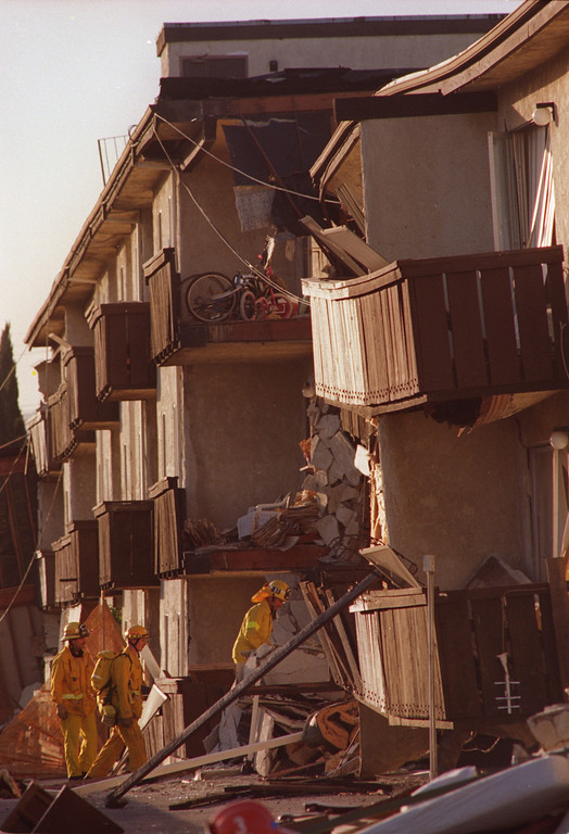 """. Firefighters work to free trapped residents at the Northridge Meadows Apartments on Reseda Blvd in Northridge CA.  The Northridge quake hit at 4:31 the morning of Jan. 17, 1994, a powerful jolt that flattened buildings, destroyed homes, damaged freeways, ignited fires and disrupted water and power.  The 6.7-magnitude Northridge Earthquake also killed nearly three dozen people, injured 8,700 more, caused some $20 billion in damage and shattered the nerves of millions of Southern California residents.  \""""It was like the devil was waking up ... it was a horrifying feeling,\"""" said one of the quake victims quoted in a Daily News story on Jan. 18.  (Daily News File Photo)"""