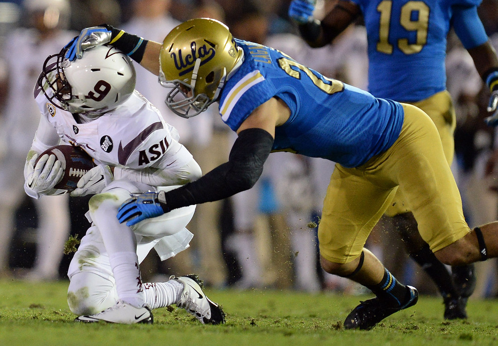 . UCLA�s Taylor Lagace #28 grabs the helmet of Arizona State�s Michael Eubank #9 during their game at the Rose Bowl Saturday November 23, 2013. Arizona State beat UCLA 38-33. (Photos by Hans Gutknecht/Los Angeles Daily News)