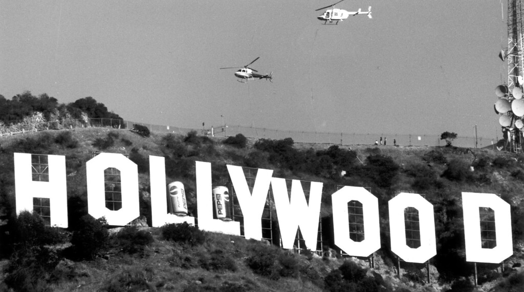 . Helicopters fly over the Hollywood sign as 20-foot-tall Pepsi cans bearing the company\'s new logo temporarily modify the historic landmark. 12/3/91 (L.A. Daily News file photo)