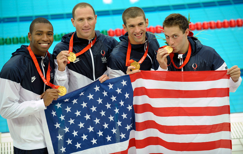 . Members of the U.S. relay team show their medals during an awarding ceremony after setting a world record to win the men\'s 4x100-meter freestyle relay final in the National Aquatics Center at the Beijing 2008 Olympics in Beijing, Monday, Aug. 11, 2008. They are from left: Cullen Jones, Jason Lezak, Michael Phelps and Garrett Weber-Gale.  (AP Photo/Thomas Kienzle)