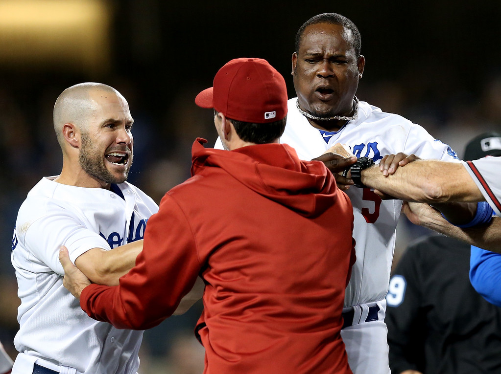 . LOS ANGELES, CA - JUNE 11: Skip Schumaker #3 (L) and Juan Uribe #5 of the Los Angeles Dodgers are restrained by pitching coach Charles Nagy of the Arizona Diamondbacks during a seventh inning benches clearing brawl at Dodger Stadium on June 11, 2013 in Los Angeles,  (Photo by Stephen Dunn/Getty Images)