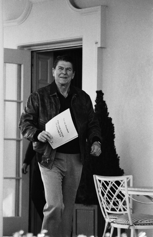 . Pres. Ronald Reagan leaves his office at the White House and points to a folder marked Presidential Statement, Saturday, Jan. 28, 1984, Washington, D.C.  (AP Photo/Ira Schwarz)