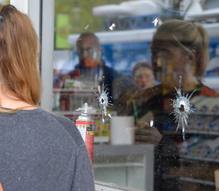 . May 24-,2014. Isla Vista, CA. UCSB students gather at IV Deli Mart were bullet holes are seen in the glass windows where one person was killed by the drive-by shooting that left seven people dead Friday night, including the attacker, and seven others wounded, authorities said Saturday.  The gunman got into two gun battles with deputies Friday night in the beachside community of Isla Vista before crashing his black BMW into a parked car. Photo by Gene Blevins/LA Daily News