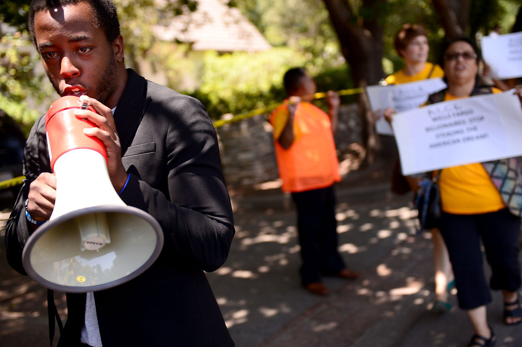 . Jace Lee leads Occupy and ACCE protesters as they descend on the home of Timothy Sloan, chief financial officer of Wells Fargo, in San Marino to protest foreclosures Saturday, July 27, 2013. (SGVN/Staff Photo by Sarah Reingewirtz)