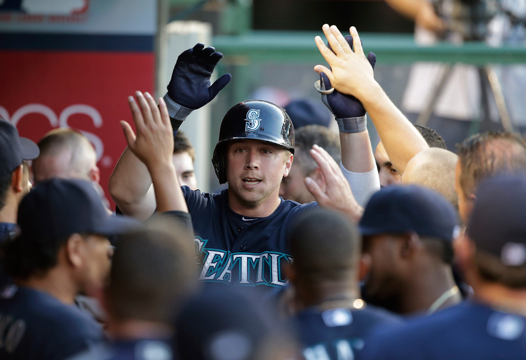 . Seattle Mariners\' Justin Smoak, center, celebrates his home run with teammates during the second inning of a baseball game against the Los Angeles Angels in Anaheim, Calif., Tuesday, June 18, 2013. (AP Photo/Jae C. Hong)