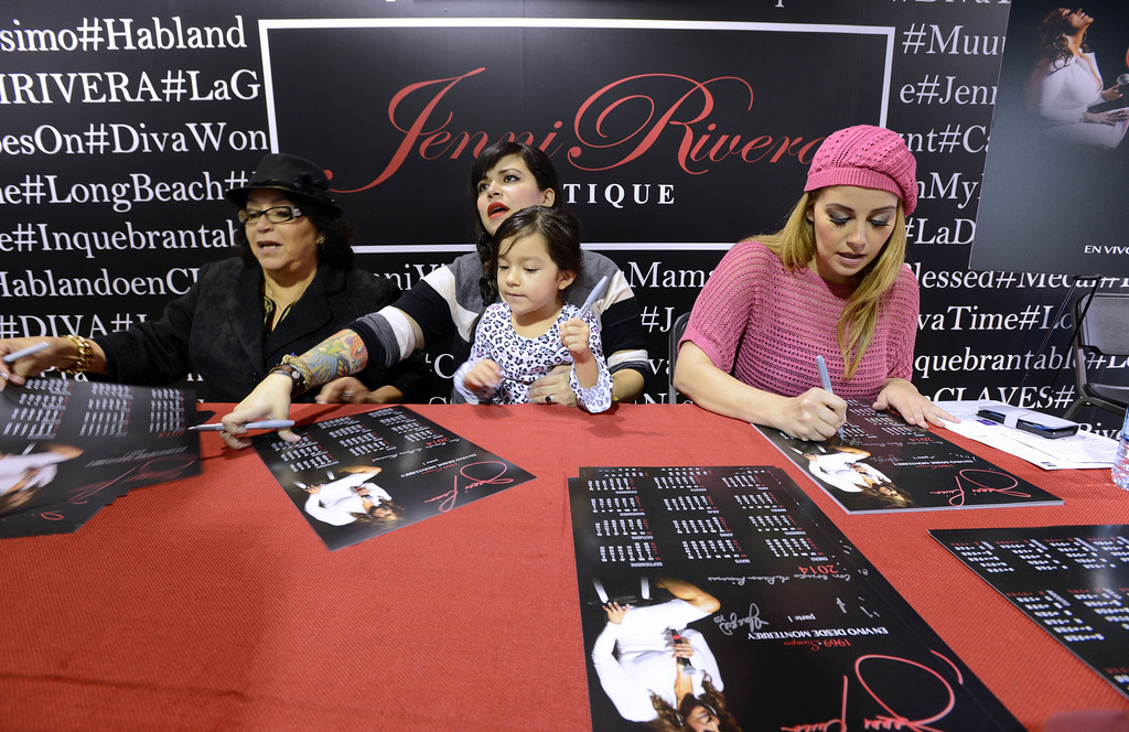 . Dec. 9 marks the one year anniversary of the death of singer Jenni Rivera. From left to right, Mother Rosa Rivera, Daughter of Jenni , Jacqui Rivera and her daughter Kayla and Jenni\'s sister Rosie Rivera sign autographs for fans inside the Jenni Rivera Boutique in Panorama City. Fans were on hand for the release of her new live album, which was recorder just before Jenni\'s death in a  plane crashed in Mexico.  Panorama City Calif., December 3, 2013.   (Photo by Stephen Carr / Daily Breeze)