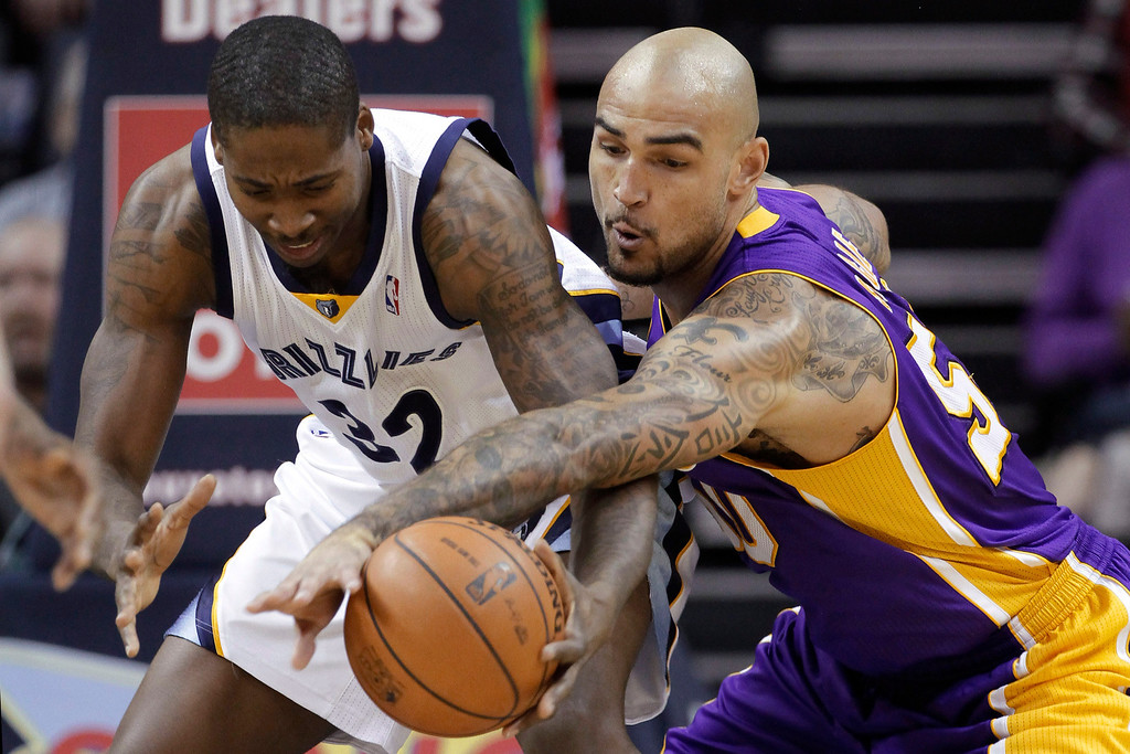 . Los Angeles Lakers\' Robert Sacre, right, gets a steal from Memphis Grizzlies\' Ed Davis (32) during the first half of an NBA basketball game in Memphis, Tenn., Tuesday, Dec. 17, 2013. (AP Photo/Danny Johnston)