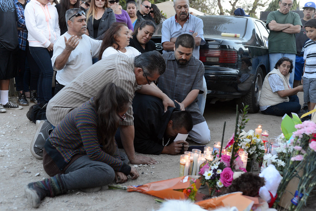 . Rudy Coronado is comforted by family, friends and neighbors during a vigil and Catholic rosary Wednesday evening for his three daughters.  Photo for The Daily Breeze by Axel Koester, 05/21/2014.