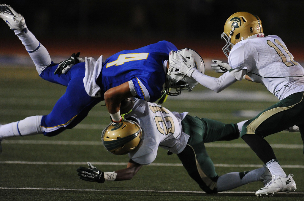 . Charter Oak\'s Donavin Washington (4) is upended by Damien\'s Cameron Record (21) as Thomas Romin (11) looks on in the first half of a prep football game at Charter Oak High School in Covina, Calif., Friday, Oct. 11, 2013.    (Keith Birmingham Pasadena Star-News)