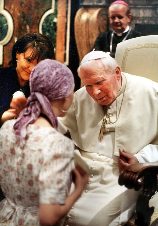 ". Pope John Paul II blesses an unidentified youth during a private audience with a group of children from Poland who are sick with cancer, at the Vatican in this June 4, 2001 file photo.  At left in background, Jolanta Kwasniewski, wife Polish President Aleksander Kwasniewski, head of the Polish foundation called ""Understanding without borders.\"" Bit by bit over his 26-year papacy, John Paul II has built a rich body of reference about the final stages of life. Its pillars include categorical rejection of euthanasia, insistence on treatments that help people bear ailments with dignity and encouragement of research to \""enhance and prolong human life.\"" But some gray areas remain. There\'s room in the pope\'s view to refuse some forms of aggressive medical intervention for terminally ill patients and avoid painkillers that induce unconsciousness. (AP Photo/Osservatore Romano/File)"