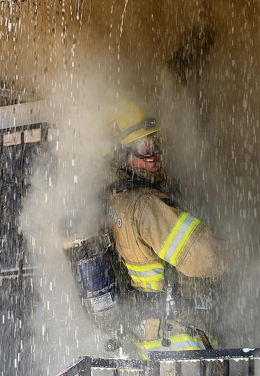 . Firefighters from San Bernardino City Fire respond to a house fire in the 700 block of 11th Street in San Bernardino. The fire apparently started near an occupied structure behind the vacant home and quickly spread. There were no reported injuries and the cause of the fire is under investigation.  (Staff photo by Rick Sforza)