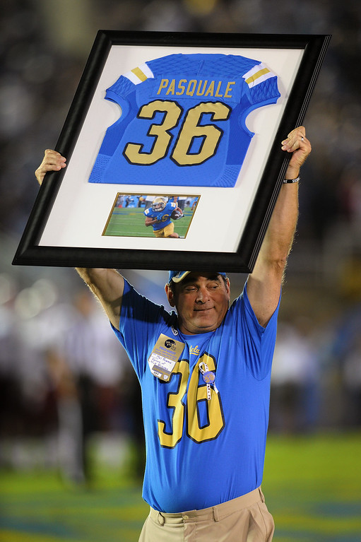 . Mel Pasquale, the father of Nick Pasquale, holds up a jersey given to his family by UCLA head coach Jim Mora and Athletic Director Dan Guerrero during the break between the first and second quarters of the UCLA -New Mexico State game, Saturday, September 21, 2013, at the Rose Bowl. The presentation took place next to the 36, Pasquale\'s number, that was painted on the field. (Photo by Michael Owen Baker/L.A. Daily News)