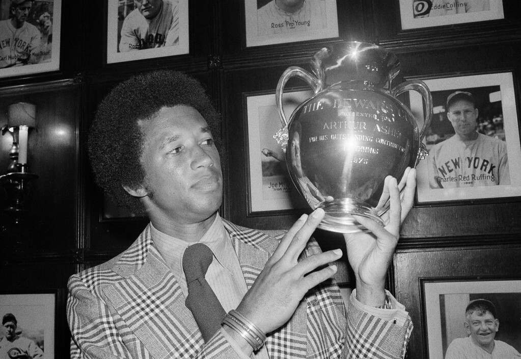 """. Wimbledon tennis champion Arthur Ashe of the U.S. admiringly looks over the Dewar Cup presented to him in New York for his \""""outstanding contribution to tennis,\"""" Aug. 26, 1975.   (AP Photo/Dave Pickoff)"""
