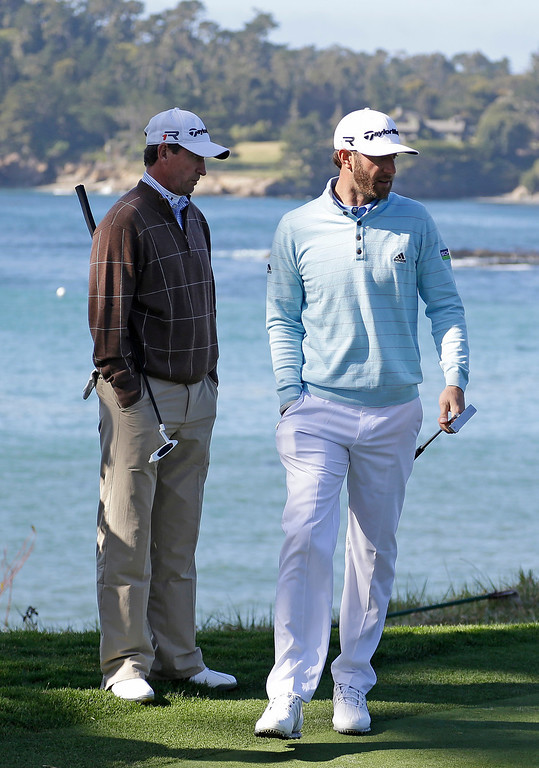 . Dustin Johnson, right, and Wayne Gretzky, left, read the fifth green of the Pebble Beach Golf Links during the third round of the AT&T Pebble Beach Pro-Am golf tournament Saturday, Feb. 9, 2013, in Pebble Beach, Calif. (AP Photo/Eric Risberg)