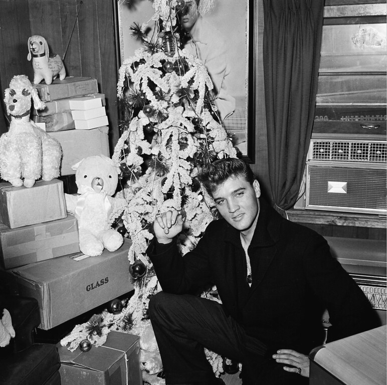. Elvis Presley poses by a Christmas tree at his home in Memphis, Tenn., in 1960. (AP Photo)