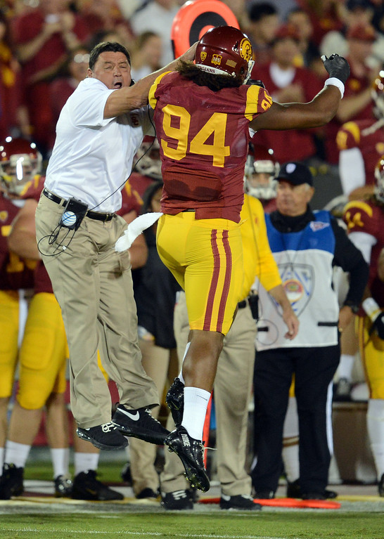 . USC interim coach Ed Orgeron high fives Leonard Williams #94 after a quarterback sack in the first quarter during their game against Arizona at the Los Angeles Memorial Coliseum Thursday, October 10, 2013. (Photo by Hans Gutknecht/Los Angeles Daily News)