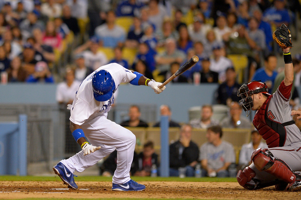 . Los Angeles Dodgers\' Yasiel Puig, left, is grazed by a pitch as Arizona Diamondbacks catcher Miguel Montero catches during the sixth inning of their baseball game, Tuesday, June 11, 2013, in Los Angeles.  (AP Photo/Mark J. Terrill)