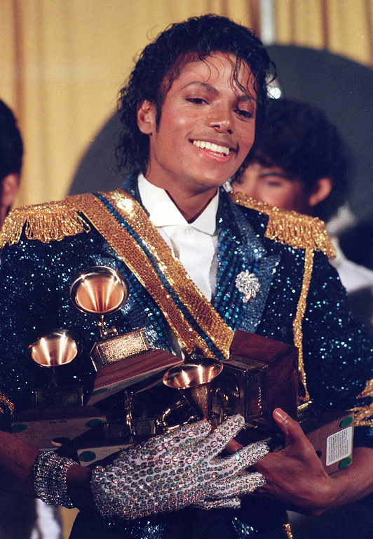 . Michael Jackson is seen backstage at the 26th annual Grammy Awards in Los Angeles Tuesday, Feb. 28, 1984, as he poses with the awards he won in eight different categories. (AP Photo/Reed Saxon)