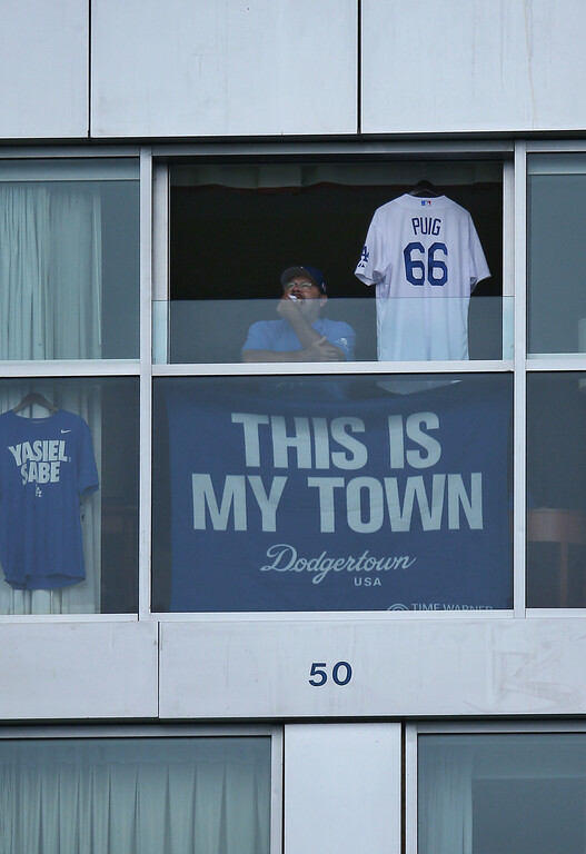 . JULY 22: A Dodgers fan hangs the jersey of Yasiel Puig #66 of the Los Angeles Dodgers from the hotel window during batting practice before MLB game action against the Toronto Blue Jays on July 22, 2013 at Rogers Centre in Toronto, Ontario, Canada. (Photo by Tom Szczerbowski/Getty Images)