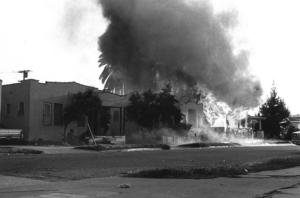 . Police wearing gas masks and bullet-proof vests charge toward a house in south-central Los Angeles May 17, 1974.  The police fired tear gas shells in the belief that the house was occupied by three members of the Symbionese Liberation Army.  They found no one inside. (AP Photo)