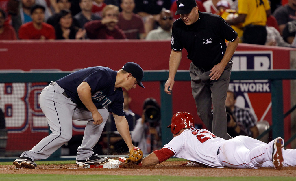 . Seattle Mariners third baseman Kyle Seager, left, puts on a tag with third base umpire Gerry Davis, right, looking on as he calls Los Angeles Angels\' Mike Trout, center, safe, for a triple, in the fourth inning during a baseball game Tuesday, May 21, 2013 in Anaheim.    (AP Photo/Alex Gallardo)