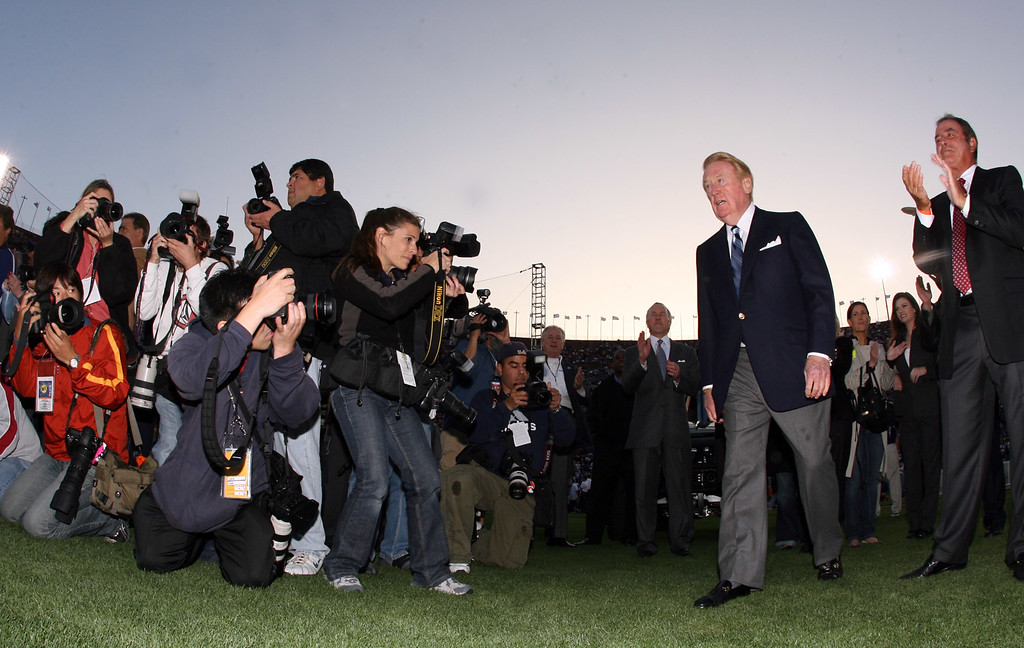 . The Dodgers long time Hall of Fame broadcaster Vin Scully walks to the podium before being honored during pre-game ceremonies for his six-decades of service to the Dodgers with a commemorative bronze plaque at the peristyle entrance to the coliseum. Scully called games at the coliseum from 1958-1961 and his 59 years of service is a Major League Record. The Dodgers celebrating there 50th season in Los Angeles played an exhibition game against the Boston Redsox\'s March 29. 2008 at the Los Angeles Memorial Coliseum. (SGVN/Staff Photo Keith Birmingham/SXSports)