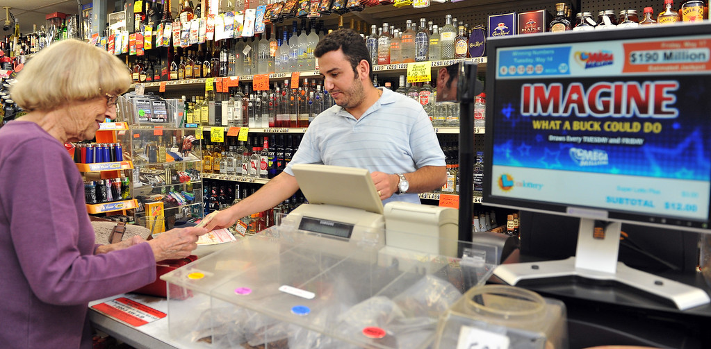. 5/17/13 - Sandi McGrath purchases Powerball tickets from George Alishak at Dick\'s Palm Tree Liquor Food Mart in Long Beach. McGrath purchased three Powerball tickets and will use the winning to buy 11 houses for her grandchildren, then donate to charity and help others in need. The jackpot for Saturdays drawing is at $550 million. Photo by Brittany Murray / Staff Photographer