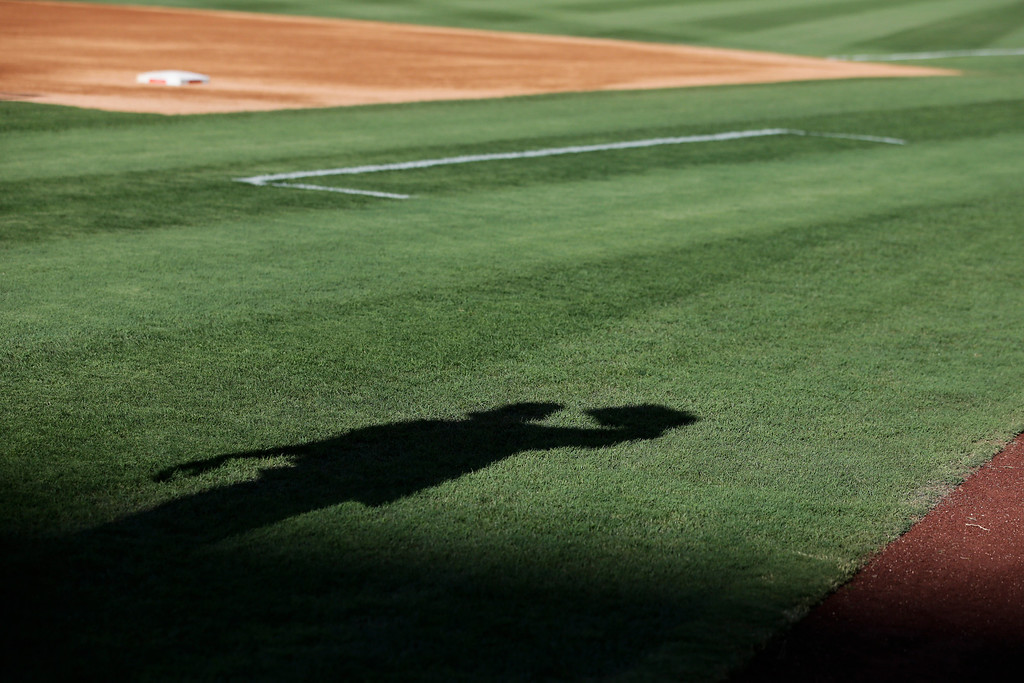 . The shadow of Houston Astros\' Robbie Grossman is casted on the field as he warms up before a baseball game against the Los Angeles Angels on Friday, Aug. 16, 2013, in Anaheim, Calif. (AP Photo/Jae C. Hong)