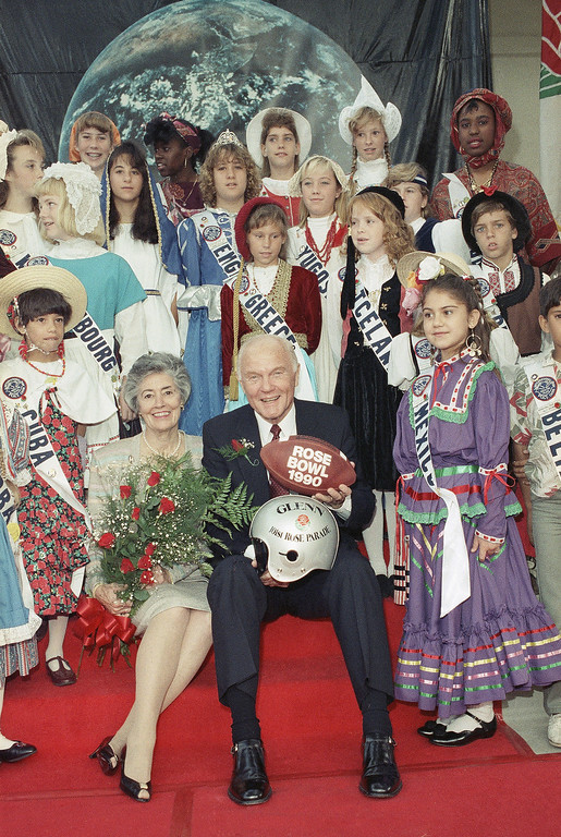 """. Sen. John Glenn (D-Ohio) and his wife, Annie, are surrounded by youngsters representing different countries of the world after he was named Grand Marshal of the 101st Rose Parade in Pasadena, California, Thursday, Oct. 12, 1989. The theme of the parade is \""""A World of Harmony.\"""" Glenn was the first American to orbit the earth. (AP Photo/Nick Ut)"""