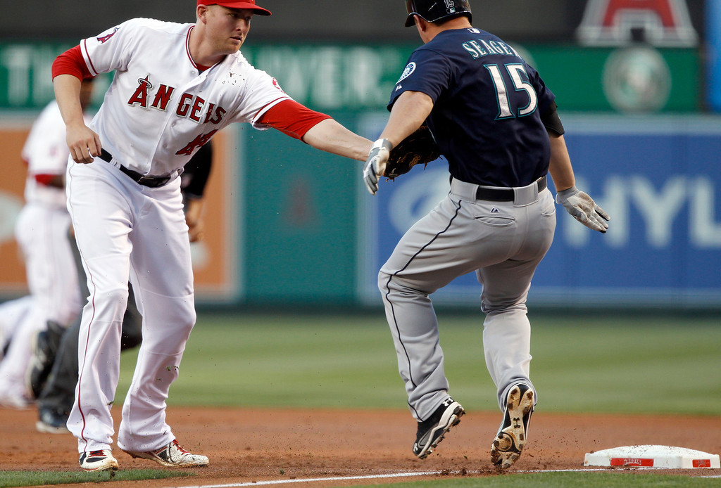 . Los Angeles Angels first baseman Mark Trumbo, left, tags out Seattle Mariners\' Kyle Seager (15) on a ground ball to the pitcher in the first inning during a baseball game Tuesday, May 21, 2013 in Anaheim.    (AP Photo/Alex Gallardo)