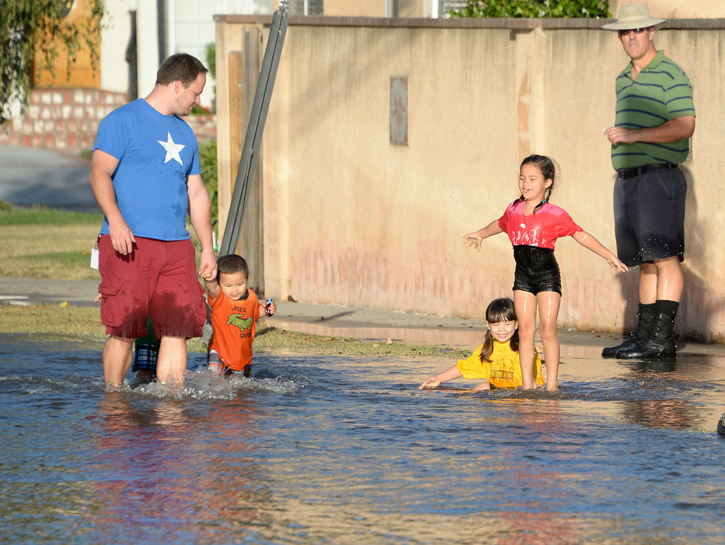 . June 17,2014. Burbank. CA. Kids have fun in the water after a 30 inch water main broke at the Burbank Fire training center Tuesday. The water created a river in the streets that were near by the brake but did not flood any homes near by. Burbank water and power crews are on scene working to shut off the water.  Photo by Gene Blevins/LA DailyNews