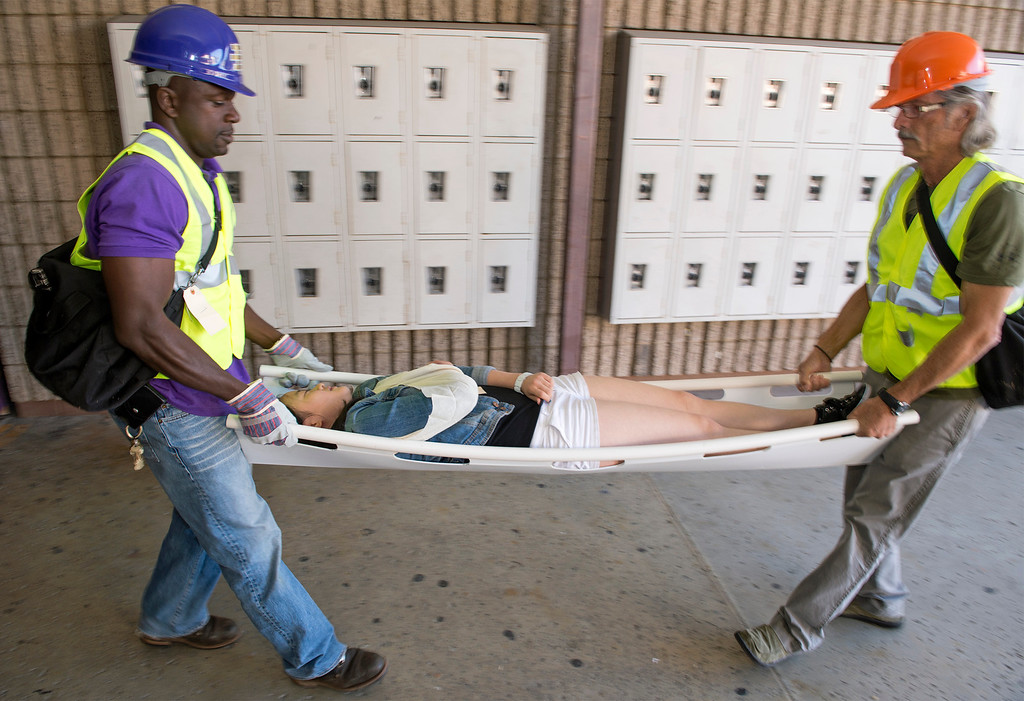 """. Diamond Bar High staff members Noel Foly, left, and David Hamel carry an \""""injured\"""" student to triage during the Great ShakeOut earthquake drill at the Diamond Bar campus October 17, 2013.  (Staff photo by Leo Jarzomb/SGV Tribune)"""