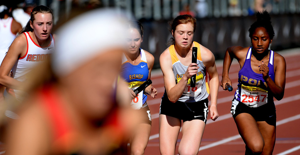 . Long Beach Poly\'s Janice Lane, right, during the 4x800 meter relay invitational race during the Arcadia Invitational track and field meet at Arcadia High School in Arcadia, Calif., on Friday, April 11, 2014. Clovis North won the race.  (Keith Birmingham Pasadena Star-News)