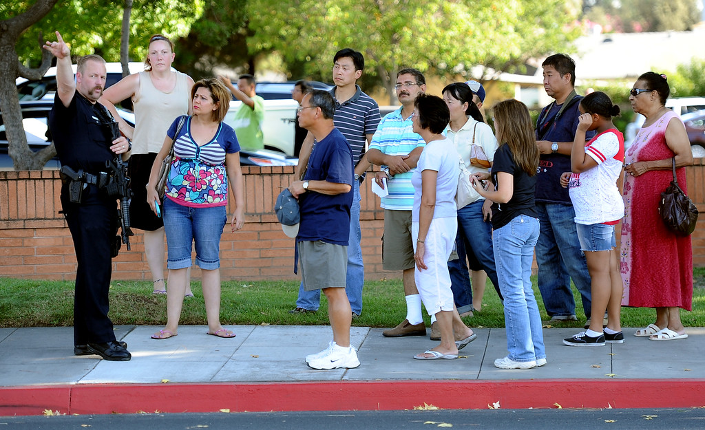 . A Arcadia Police officer advises parents to wait for their children at Arcadia County Park after a lockdown at Arcadia High School in Arcadia, Calif. on Thursday, Sept. 12, 2013.   (Photo by Keith Birmingham/Pasadena Star-News)