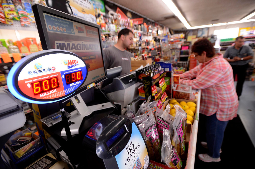 ". Gloria Ybarra, of Fontana, buys a Powerball ticket at Quicker Liquor along Sierra Avenue in Fontana May 17, 2013.  ""Six hundred million dollars is a lot of money,\"" said Quciker Liquor Store Manager Essa Mubarakah, says about the Powerball Lottery.  Nearly 40 people have purchased tickets by mid-day at the Fontana store.  The store displays past winning tickets at the lottery display. \""We put them up for everybody to see ,\"" says Mubarakah, \""so they can know that they have a chance to win here. Its a lucky store.\""  The Powerball Lottery, which California just joined earlier this year, is at $600 million for Saturday\'s drawing.  It is the third-highest jackpot in U.S. history.  GABRIEL LUIS ACOSTA/STAFF PHOTOGRAPHER."