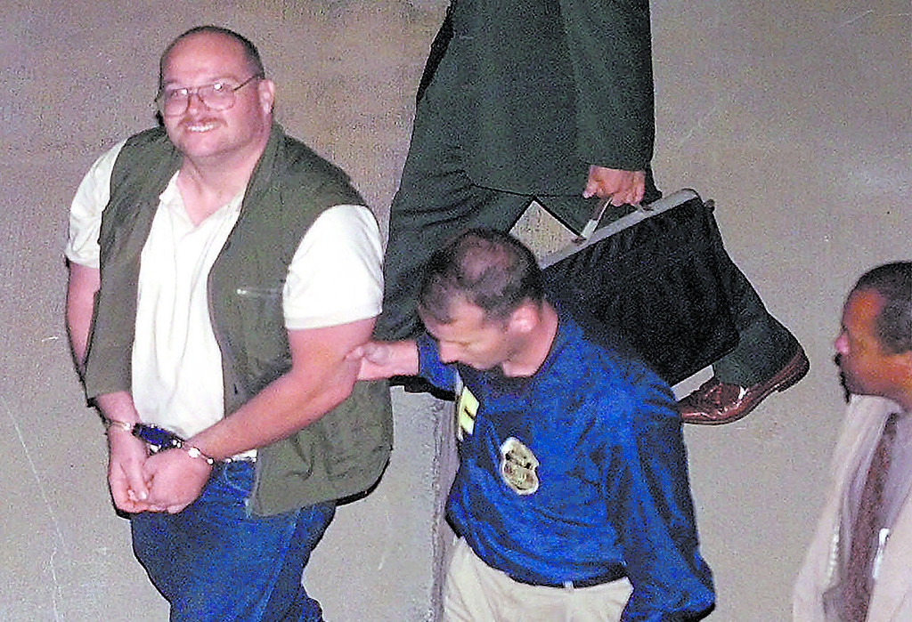 . Buford O. Furrow Jr., 37, is escorted by federal officials as he arrives in Los Angeles late Wednesday, Aug. 11, 1999.  Furrow was transported from Las Vegas aboard a U.S. customs Blackhawk helicopter after waiving extradition in Las Vegas.  He faces five charges of attempted murder as well as a murder charge in the killing of a postal worker in the shootings Tuesday at a Jewish community center in Los Angeles. (AP Photo)