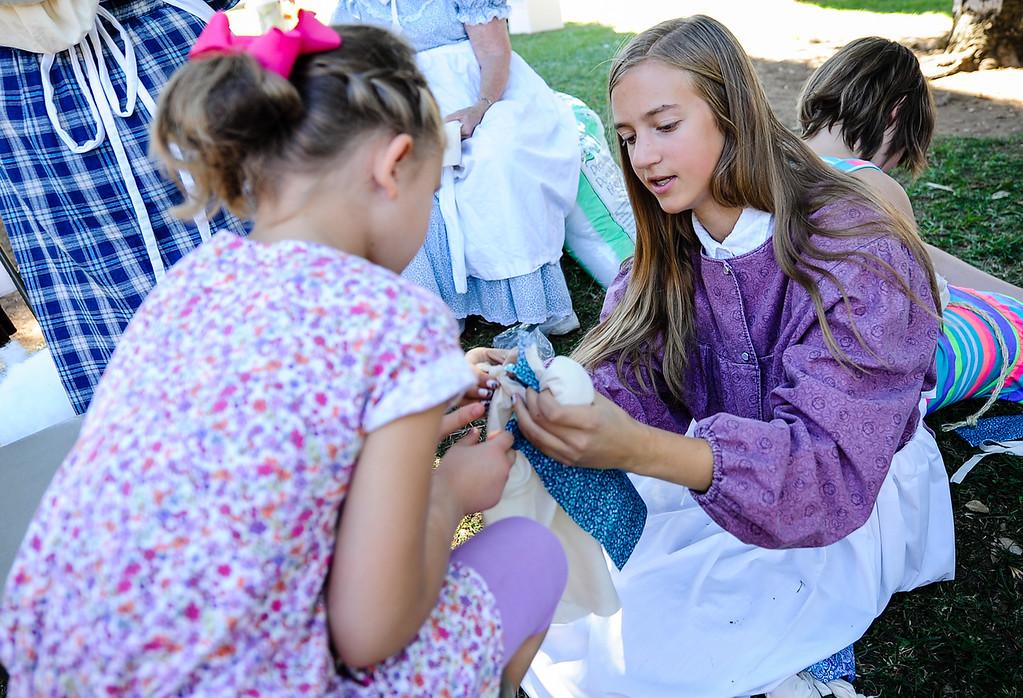 . Maia (cq) Richards-Dinger, 15, right, volunteers at the doll making both at the Redlands 125th anniversary celebration on Saturday, Nov. 2, 2013. (Photo by Rachel Luna / San Bernardino Sun)