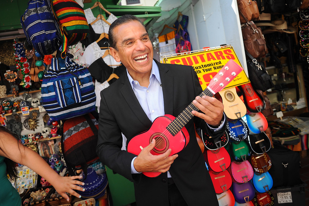 . Mayor Antonio Villaraigosa lets out a smile while strumming a toy guitar at Olvera Street in Los Angeles, CA June 28, 2013.  Villaraigosa spent the day visiting some of his favorite loactions during his 24-hour goodbye tour.(Andy Holzman/Los Angeles Daily News)